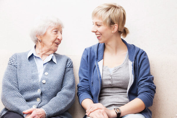 Social worker smiles at elderly woman